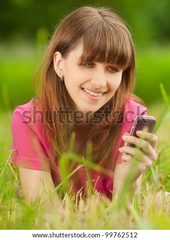 Beautiful young woman with mobile phone lies on green grass at summer green park