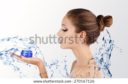 Beautiful young woman with moisturizing cream and water splash isolated on white - stock photo