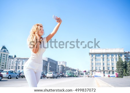 Beautiful young woman with music headphones around her neck, taking picture of herself, selfie against urban city background.