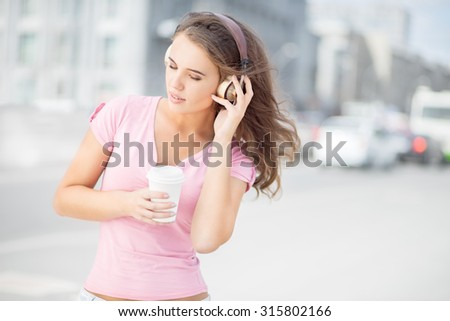 Beautiful young woman with music headphones, holding a take away coffee cup and listening to the music with her eyes closed against city traffic background. - stock photo