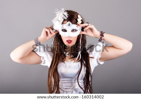 beautiful young woman with mysterious venetian mask - stock photo