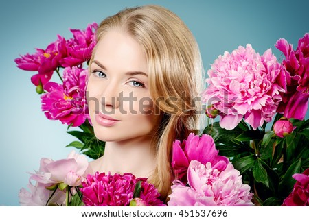 Beautiful young woman with natural make-up and long blonde hair holding a peony flowers. Beauty, fashion, cosmetics. Copy space.