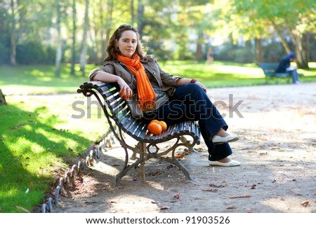 Beautiful young woman with oranges in park at spring or fall