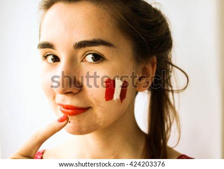 Beautiful young woman with painted austria chile flag on face football olympic games supporter - stock photo