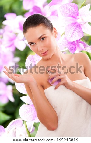 Beautiful young woman with parfume - stock photo