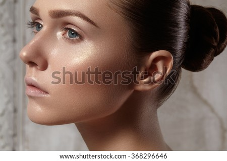 Beautiful young woman with perfect clean shiny skin, natural fashion makeup. Glamour portrait of model with cute bun hairstyle. Close-up woman, fresh spa look  - stock photo