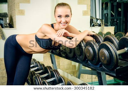 Beautiful young woman with perfect figure is training with dumbbells at the gym. Active lifestyle, bodycare. Fitness equipment. - stock photo