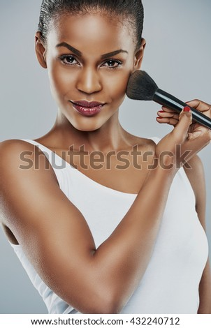 Beautiful young woman with perfect skin applying makeup with a brush against a gray background - stock photo