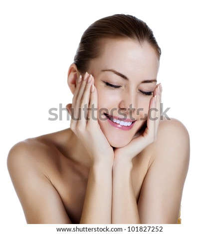 Beautiful young woman with perfect skin. She laughs, hiding her face in her hands - stock photo