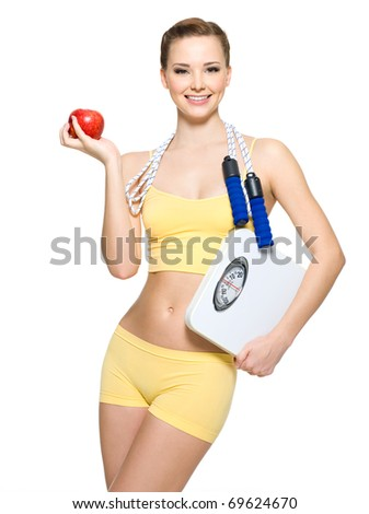 beautiful young woman with perfect sporty body holding scales and apple - stock photo