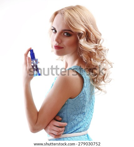 Beautiful young woman with perfume bottle isolated on white - stock photo