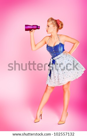 Beautiful young woman with pin-up make-up and hairstyle looking through binoculars over pink background. - stock photo