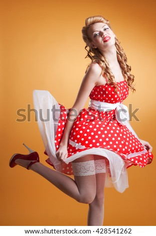 Beautiful young woman with pin-up make-up and hairstyle posing in studio - stock photo