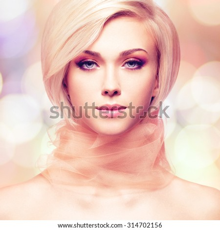 Beautiful young woman with pink fabric posing at studio on creative background. - stock photo