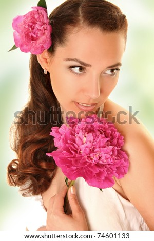 beautiful young woman with pink flower on green