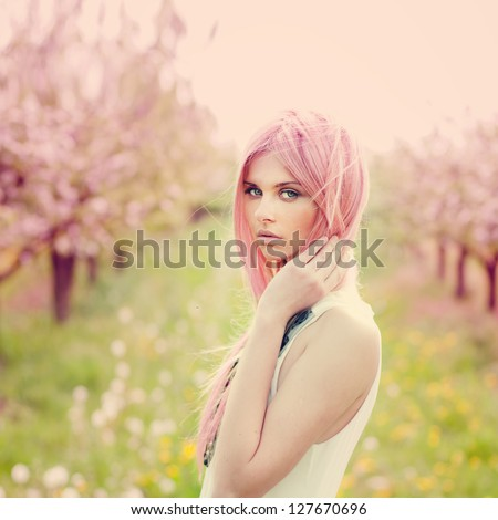 beautiful young woman with pink hair and sensual look in the garden in summer - stock photo