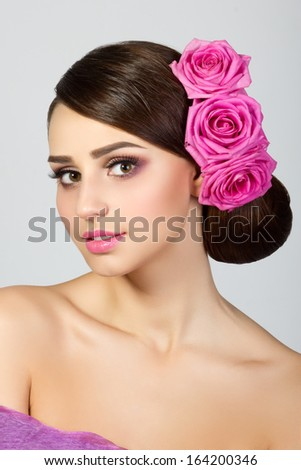 Beautiful young woman with pink roses in her hair - stock photo