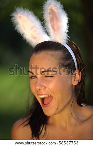 Beautiful young woman with playboy rabbit ears on nature - stock photo