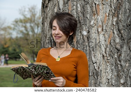 Beautiful young woman with reading a book on tree background  - stock photo