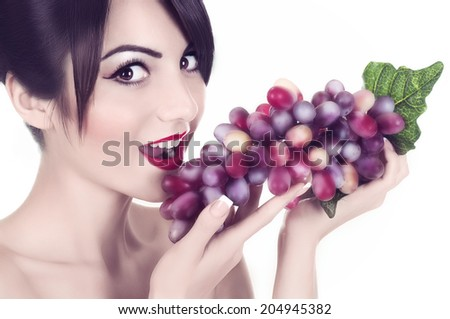 Beautiful young woman with red grape on white background. - stock photo