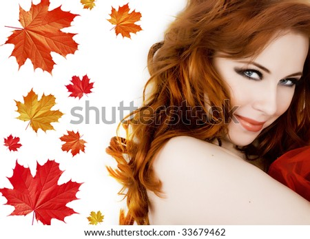 Beautiful young woman with red hair amd maple leaves - stock photo