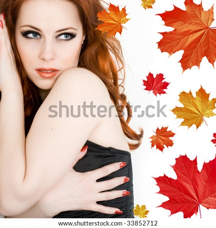 Beautiful young woman with red hair and maple leaves - stock photo