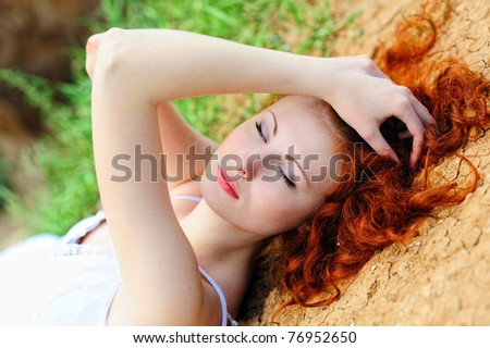 Beautiful young woman with red hair laying on the ground. - stock photo