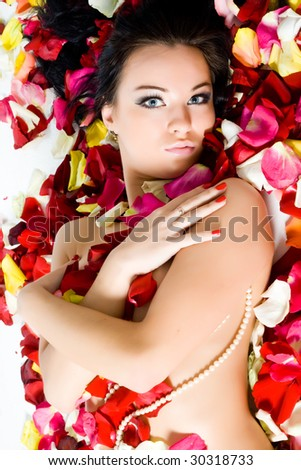 Beautiful young woman with rose petals - stock photo