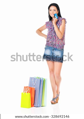 Beautiful young woman with shopping bags and credit card or gift card, isolated over white background