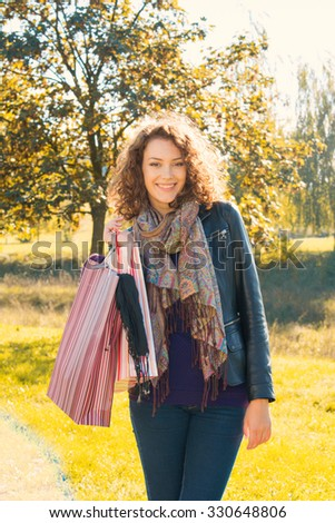 Beautiful young woman with shopping bags and yellow leaves in background - stock photo