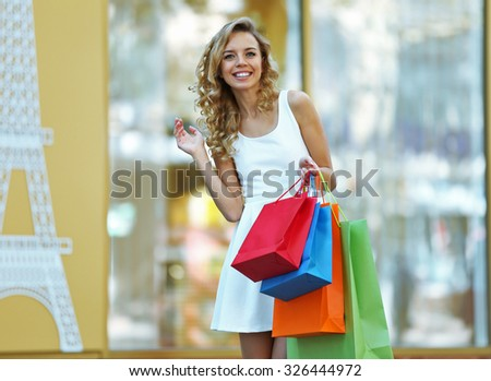Beautiful young woman with shopping bags on city street