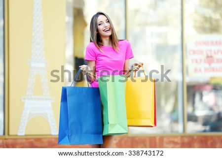 Beautiful young woman with shopping bags on city street - stock photo