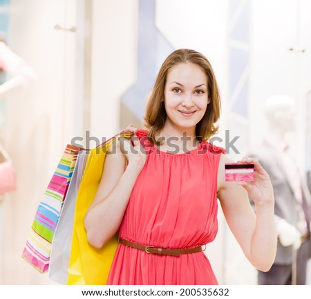 Beautiful young woman with shopping bags showing credit card