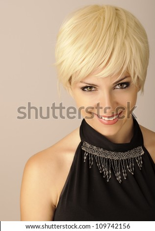Beautiful young woman with short blond hair looking at camera and smiling - stock photo