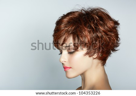 beautiful young woman with short brown haircut wears pink lipstick on studio background with copy space. - stock photo