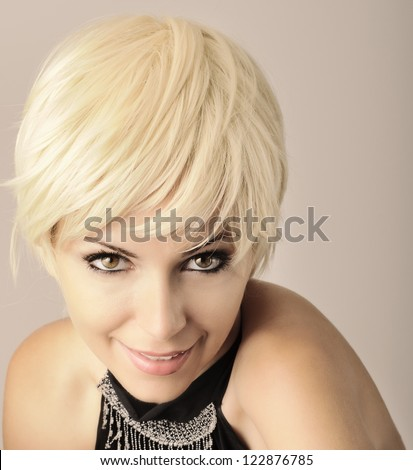 Beautiful young woman with short pixie light blond hair looking at camera and smiling