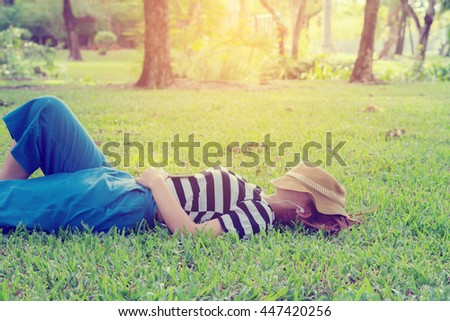 Beautiful young woman with sleeping listen to music in the park,vintage tone  - stock photo
