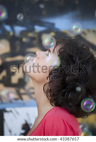 Beautiful young woman with soap-bubbles - stock photo