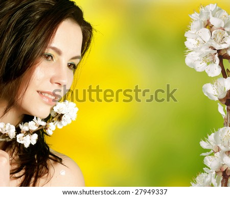 Beautiful young woman with sprig flower over abstract blurred background
