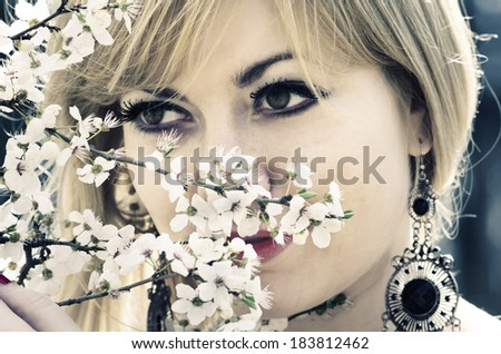 Beautiful young woman with spring blossoms. Retro filter. - stock photo