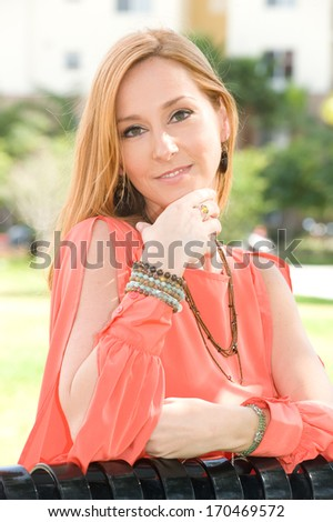 Beautiful young woman with strawberry blond hair smiling outdoors - stock photo