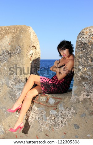 beautiful young woman with stylish dress on a wall close to the sea - stock photo
