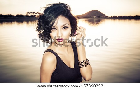 Beautiful young woman with stylish short hair in tropical location - stock photo