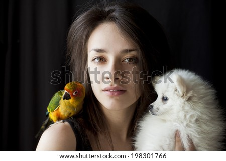 Beautiful young woman with sun conure on her shoulder and holding a puppy - stock photo