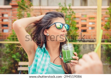 Beautiful young woman with sunglasses drinking green vegetable smoothie with straw in a summer day outdoors. Healthy organic drinks concept. - stock photo