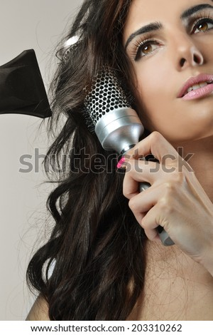 Beautiful young woman with the hair dryer and brush - stock photo
