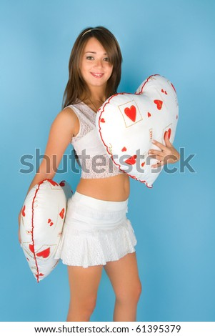 Beautiful young woman with two heart shaped pillows - stock photo