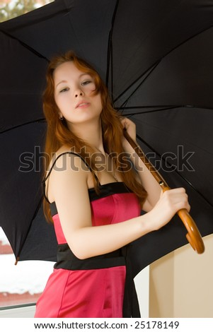 Beautiful young woman with umbrella in room