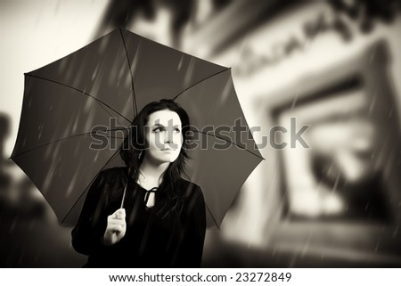 Beautiful young woman with umbrella on rainy day