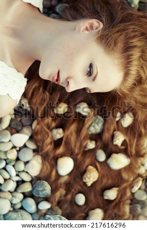Beautiful young woman with unusual hairstyle on beach. Fashion photo - stock photo